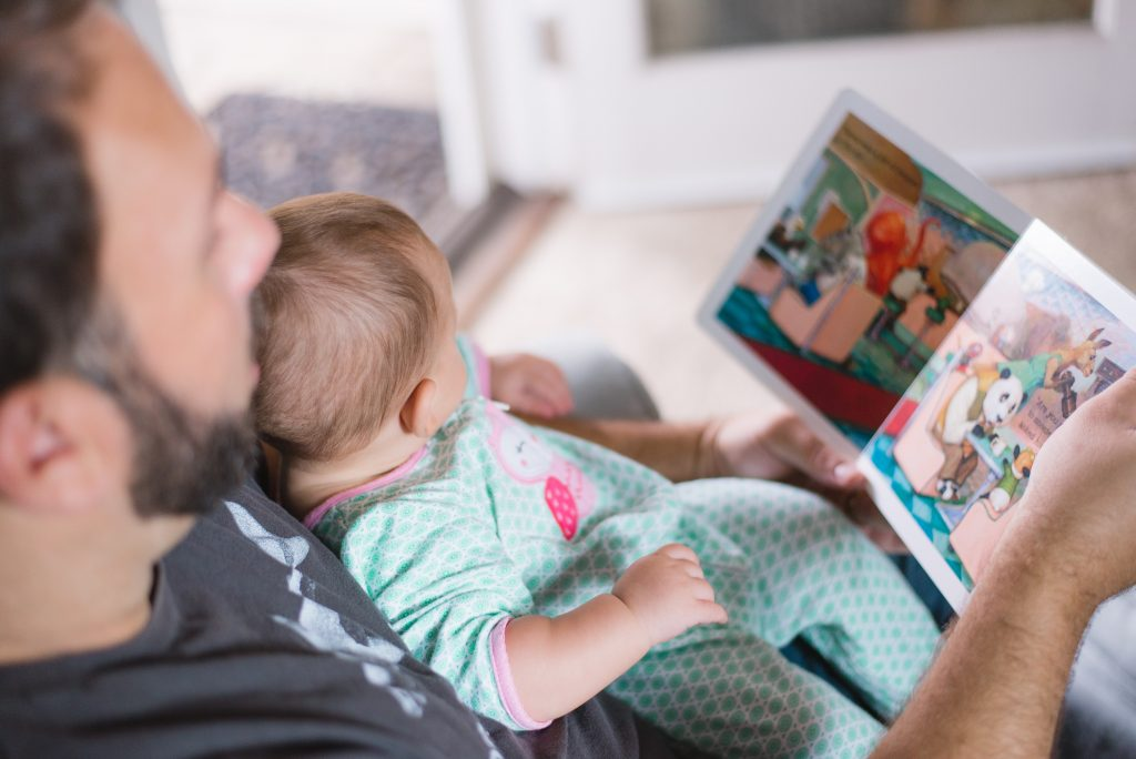 man holding a young infant on his lap reading a book